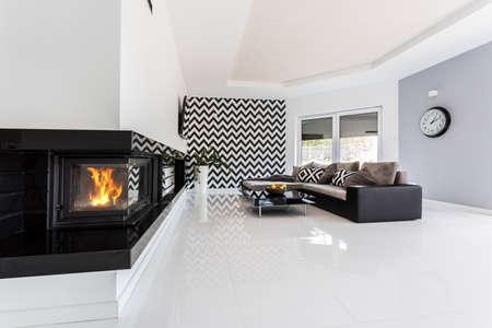 Lichte en ruime luxe woonkamer met open haard, grote bank, kleine tafel en patroon behang