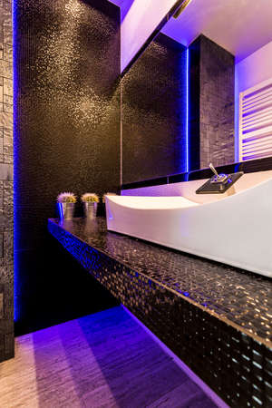 Modern style bathroom with black tiling, countertop basin and mirror Stock Photo