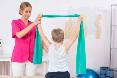 Physiotherapist and small boy back view exercising with a resistance band