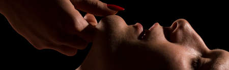 erotic woman: Close shot of womans hands with long, red nails, touching mans chin Stock Photo
