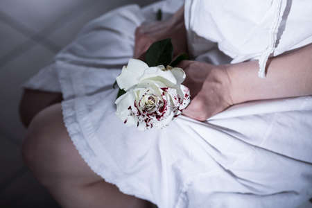 obscurity: Woman is sitting on a chair and holding a bloody white roses