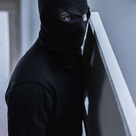 face work: Close-up of a thief in a black balaclava stealing a painting Stock Photo