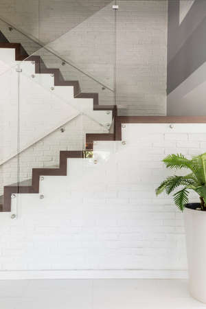 Image of luxurious white villa staircase with glass balustrade and chromed railing Stock Photo