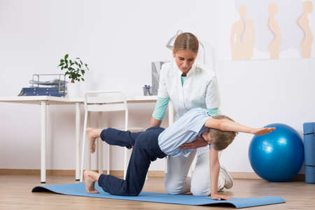 Small boy exercising with professional physiotherapist in a light medical office