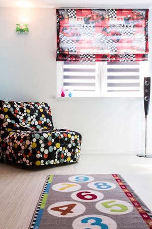 stanza del bambino con divano letto modello, moquette e finestre avvolgibili
