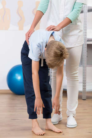 curvature: Close up of a doctor checking boys spine curvature