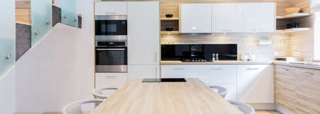 muebles de madera: Disparo de una moderna cocina espaciosa con muebles blancos y de madera Foto de archivo