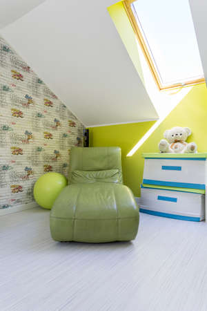 green couch: Attic child room with single sofa bed, white commode, window and wallpaper