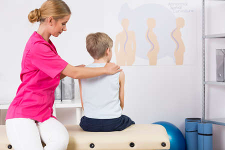 body posture: Physiotherapist correcting body posture of a small boy