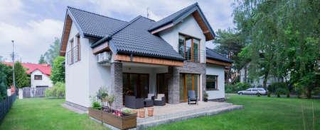 Opname van een wit vrijstaand huis en zijn tuin