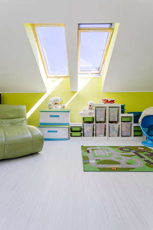 storage unit: Modern style attic child room in white and green with sofa and new storage unit Stock Photo