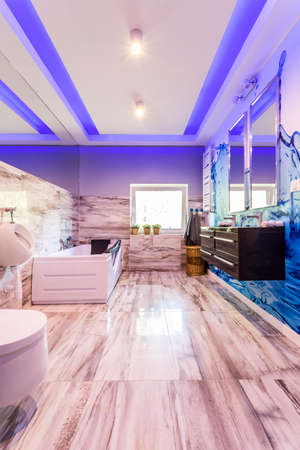 lightings: Spacious villa bathroom with marble tiling, toilet, bidet, bathtub, two basins and two mirrors