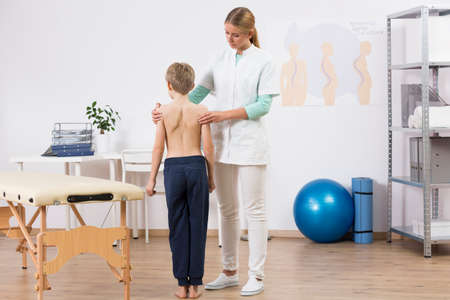 body posture: Doctor correcting small boys body posture, standing in well equipped physiotherapist office