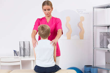 body posture: Small boy back view sitting on an exam table and physiotherapist correcting his body posture