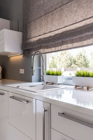 Image of high gloss white modern kitchen with window roller blinds