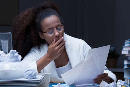 backlog: Tired young woman yawning and working late at home Stock Photo
