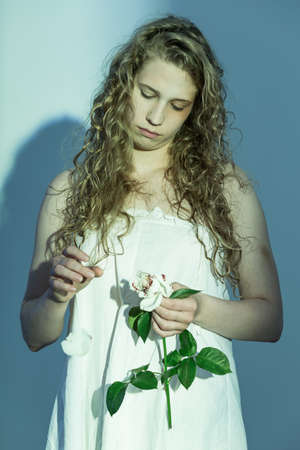 obscurity: Sad and pensive woman torns white rose petals Stock Photo