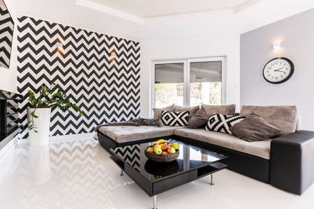 room: New style spacious living room with large sofa, black small table and pattern wallpaper
