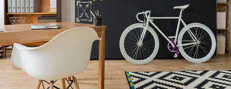 bike cover: Shot of a cozy interior with a white chair and a bike against a blackboard wall Stock Photo