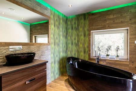 Luxe badkamer met houten en stenen effect tegels, zwart bad en wastafelbekken