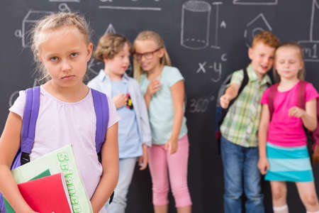 pointing fingers: Cropped shot of a sad girl standing against the background of children pointing fingers at her Stock Photo