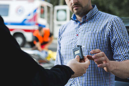 Police officer giving the breathalyser to the other man Stock Photo