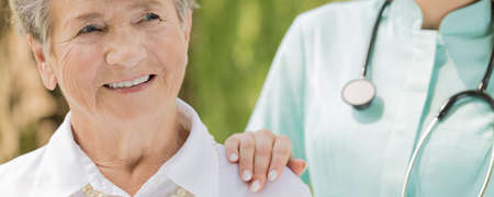 age old: Happy senior woman and female doctor with stethoscope Stock Photo