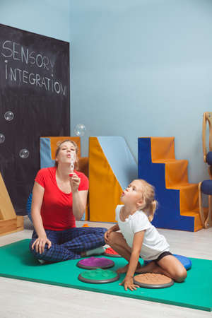 sense of sight: Girl sitting ona floor close her therapist making the soap bubbles