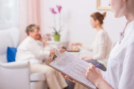 Infermiere che fa note ai risultati medici con la donna anziana sullo sfondo