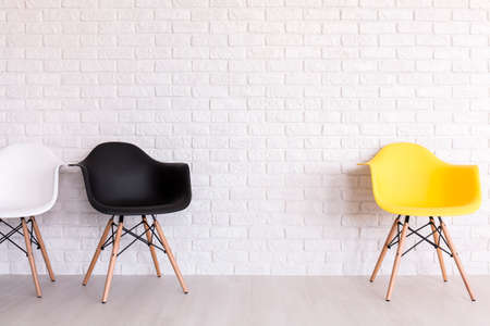 neatness: White, black and yellow chairs on the background of a white brick wall