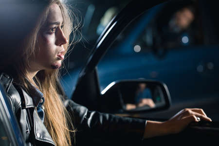 reckless: Frightened young woman with hurt face sitting in the car Stock Photo