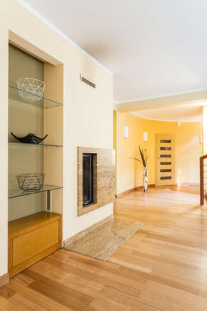 wall mounted: New villa interior in beige with floor panels and wall mounted fireplace Stock Photo