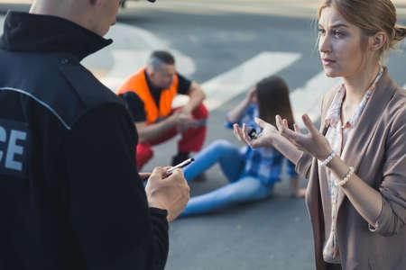 Vrouw die met de politieman met het slachtoffer van autoongeval bij de achtergrond spreekt Stockfoto