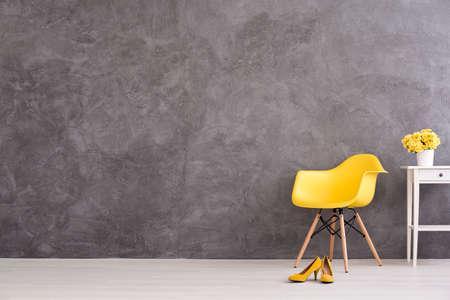 Żółte krzesło, buty i kwiaty na stole na tle szarej betonowej ścianie