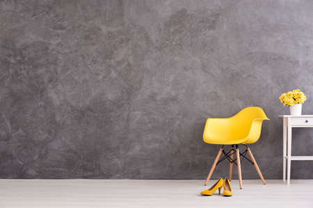 Yellow chair, shoes and flower on the table  on a background of a gray concrete wall Imagens - 60771904