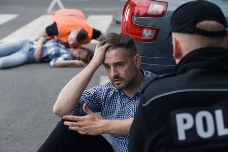 shunt: Anxious man sitting in front of the police officer with the victim of a crash at the background Stock Photo