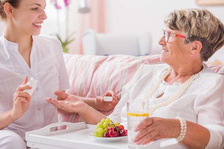 Mujer mayor que toma sus pastillas de joven enfermera sentada frente a ella
