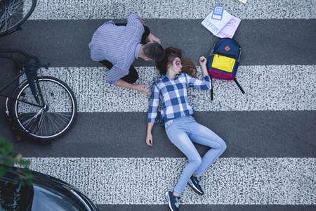 自転車と彼女の最初の援助を与える人間と道路に横たわってクラッシュの犠牲者を傷つける 写真素材