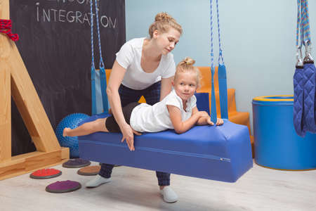 sense of sight: Girl lying on a swing with the therapist helping her to exercise