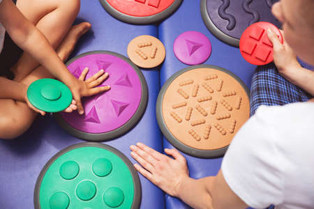 sense of sight: Girls and therapists hands touching the various shaped mat