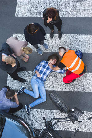 onlooker: Onlookers of car crash surrounded the accident casualty lying on the road