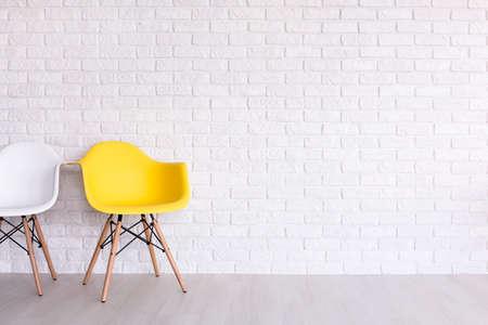 sencillez: Sillas blancas y amarillas en el fondo de una pared de ladrillo blanco