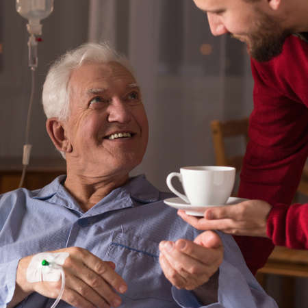 incurable: Male carer assisting incurable ill senior man Stock Photo