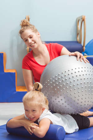 Physiotherapist massaging the girls back by big silver ball Stock Photo