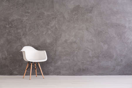 White plastic chair on a background of a gray concrete wall