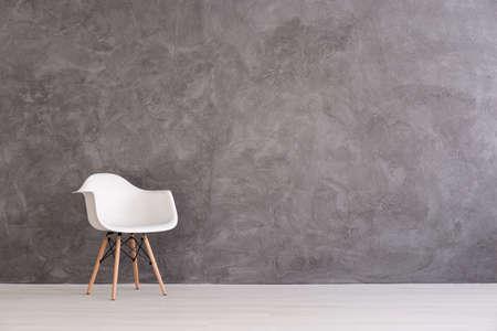 Witte plastic stoel op een achtergrond van een grijze betonnen muur
