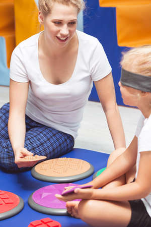 sensory: Therapist giving the sensory therapy equipment to girl with covered eyes