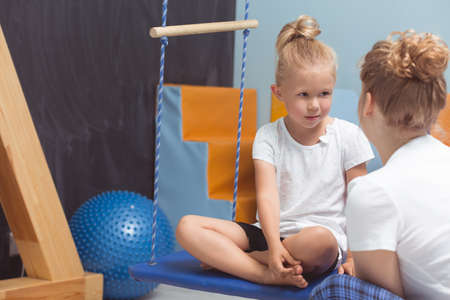 kids exercise: Woman physiotherapist talking to the young girl sitting on a swing