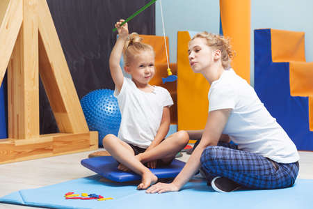 sense of sight: Sensory integration therapy interior with a girl and therapist sitting on the floor