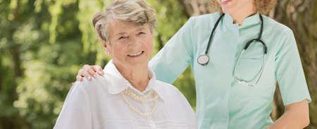 caring nurse: Cheerful elegant senior woman and female caring nurse Stock Photo